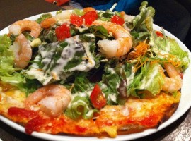 Pizza topped with king prawn, salads, tomatoes, carrots and others