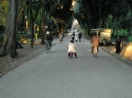 Long boulevard in Villa Borghese Rome, people biking
