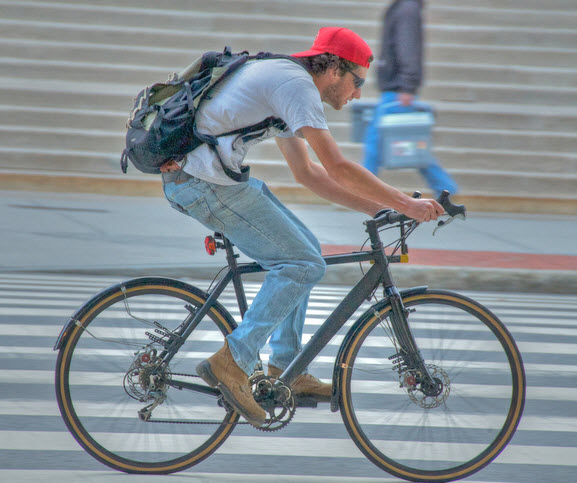 A stident of MIT biking in front of MIT entry in Cambridge , Mass USA