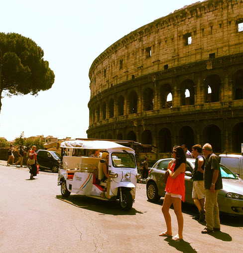 A white Tuk Tuk parked right aside the Colosseum in Rome