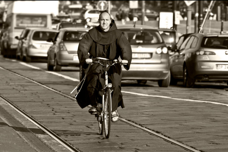 A Friar biking to job