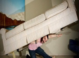 Man holding a couch on his back