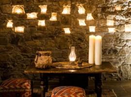 candles and wall in stones inside the Eremito Hotelito del Alma (Orvieto, TR)