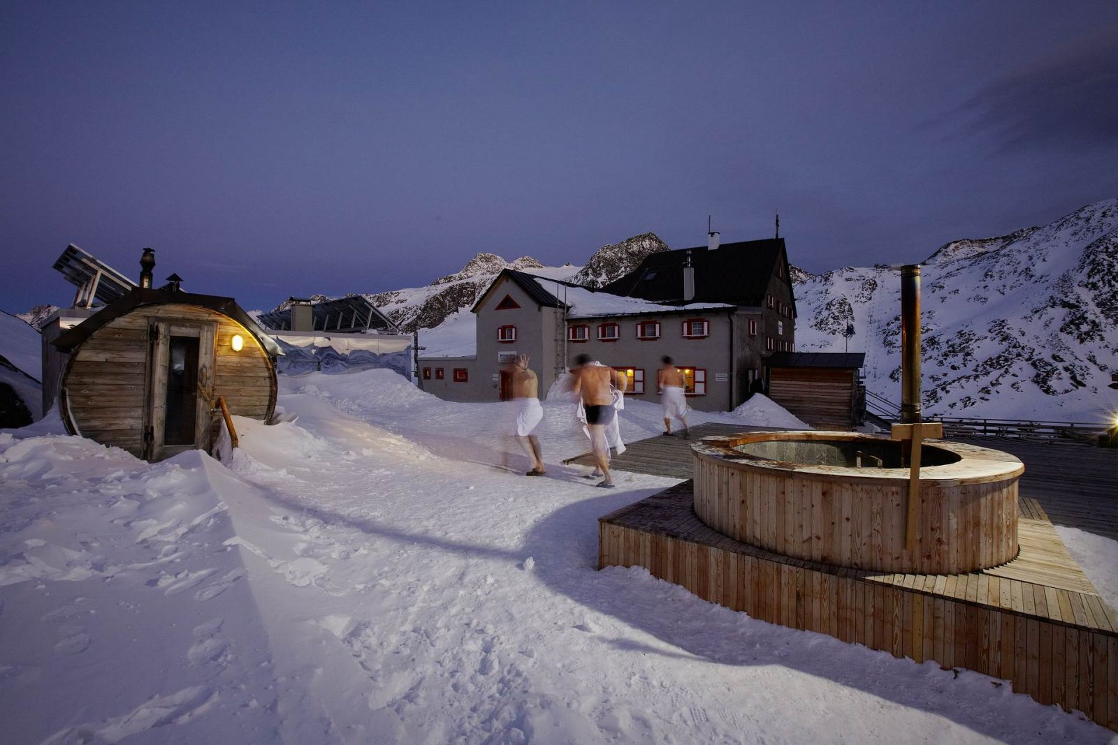 in a snowy landscape, three men are going to the refuge; on the left, there is the swedish sauna, on the right the heated pool (Refuge Bella Vista, BO)