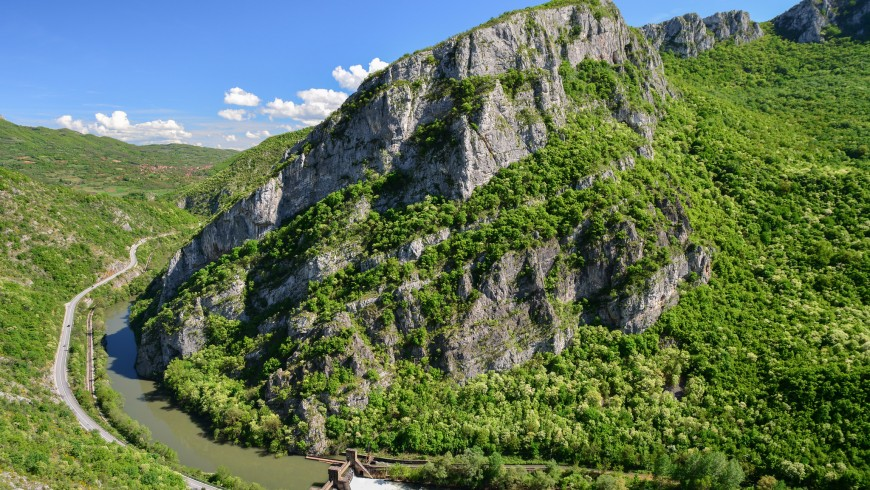 rocky peak with trees and a river in the valley