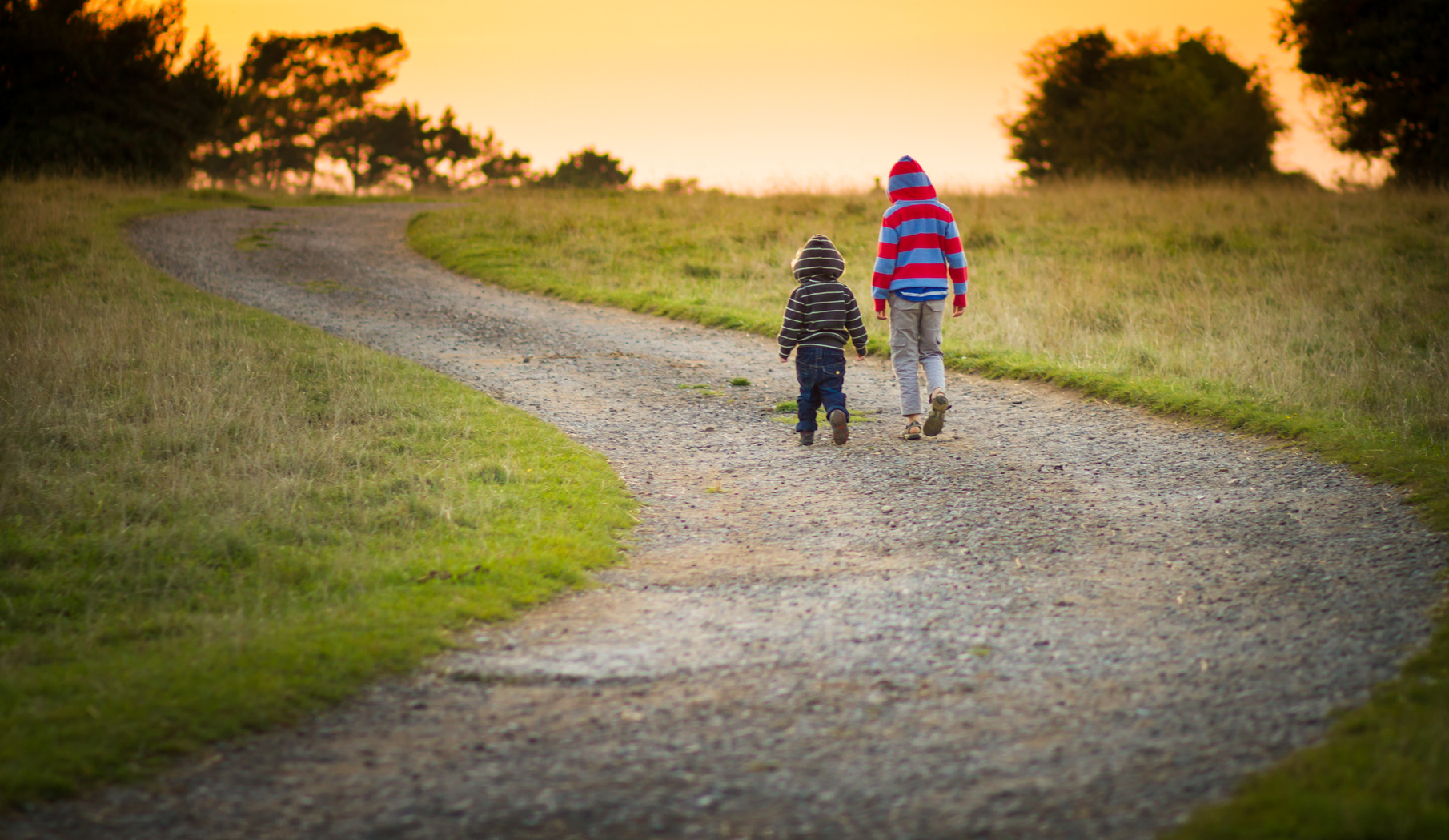 two young boys walking together down a path towards the setting sun