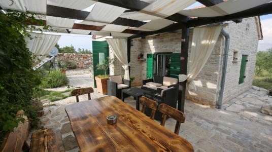 The outdoor living: wicker sofa and armchairs, the dining table with chairs, the gazebo with curtains covering the area