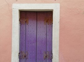 detail of a violet window in a pink house