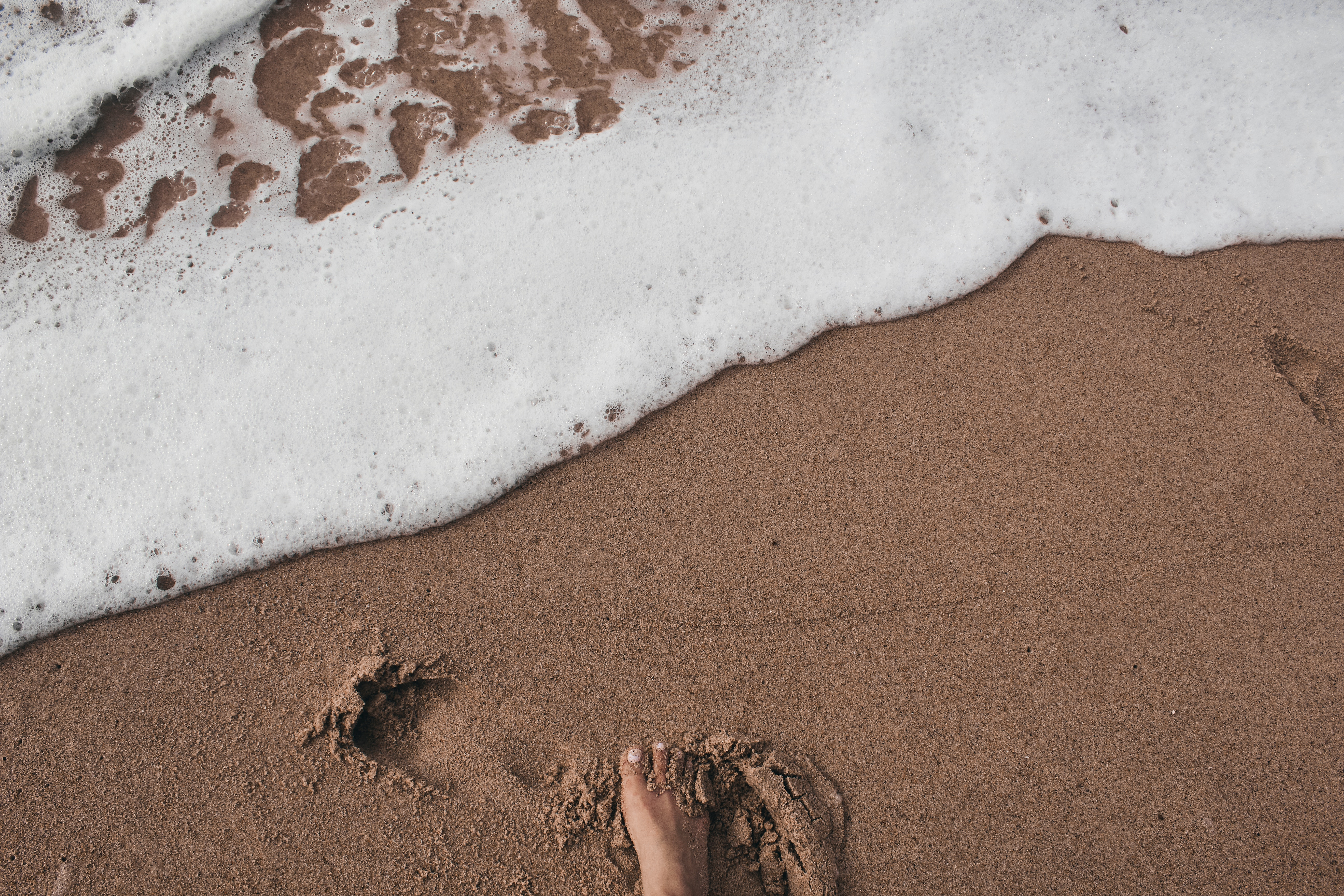 footprint on the sand. sustainable travelling is important.