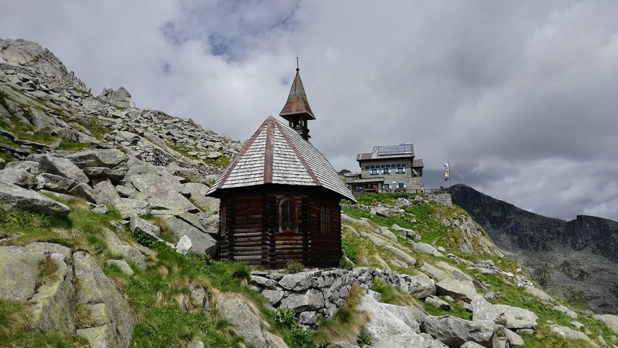 Church surrounded by rocky mountains and alpine refuge