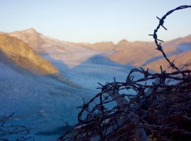 Barbed wire closeup and mountains in the background