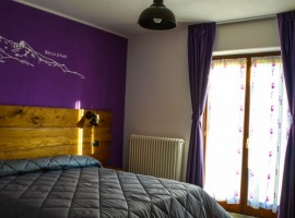 A room with a purple wall and a window with curtains