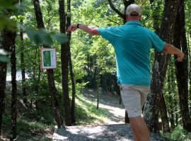 a man throwing his shot among trees