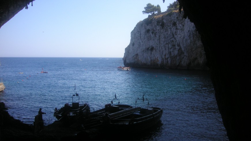 The Zinzulusa cave form inside looking atthe sea and with a boat which is about to start the tour