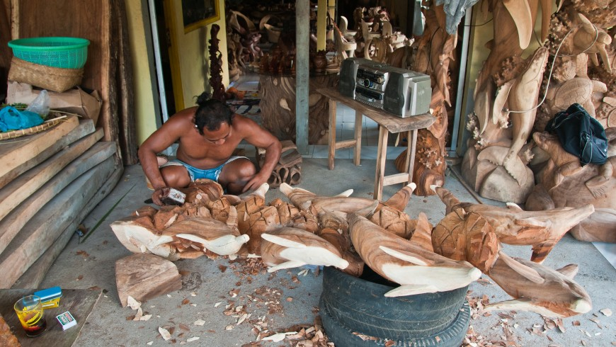 Local man working on a statue from wood.