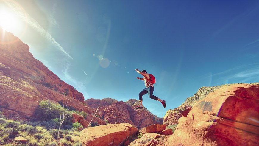 Man jumping on rocks on a hike