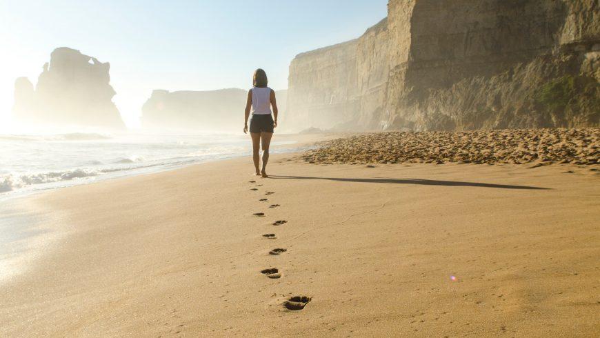 Green tourist walks on the beach