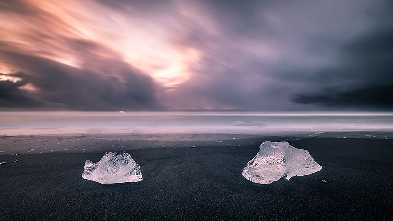 Blocks of ice on black sand, sea and pink sky in the background