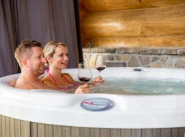 Couple tasting wine in the hot tub