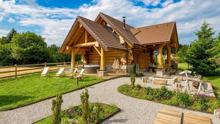 Exterior of Divjake Log Home eco chalet in Croatia, on a sunny day.