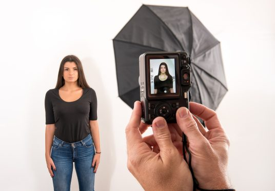 Attractive woman posing for her passport photo in a photographic studio with the photographers hands in the foreground holding the camera with viewfinder visible