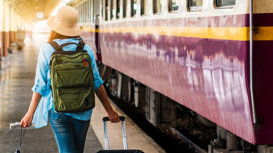 Sustainable traveler: Solo woman backpacker traveler plan safety trip low cost budget summer holiday after coronavirus. Empty tourists on train railway platforms. Use bus train sustainable environmental friendly transport