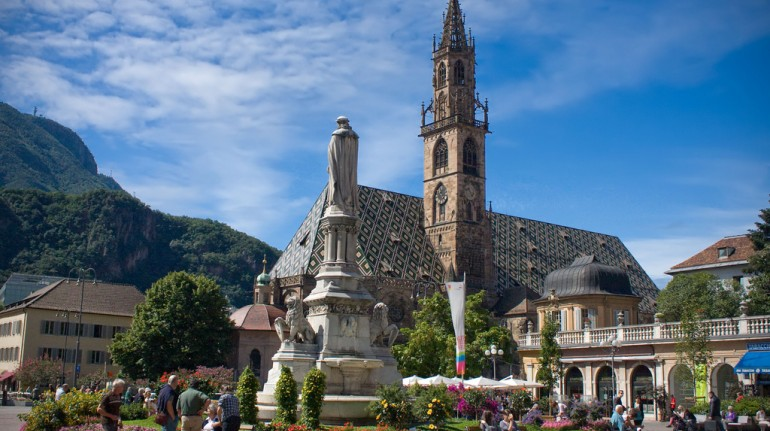 the church of bolzano with its green and gold roof and the fountain with flowers in the middle of the square